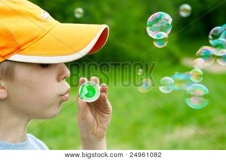 Boy blowing soap bubbles.