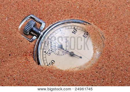 Old pocket watch in the sand of a beach.