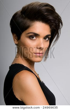 Beautiful young woman with straight short hairstyle on gray background