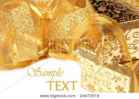 Shiny gold gift boxes and ribbon on white background with copy space.  Macro with shallow dof.  Selective focus on corner of top box.
