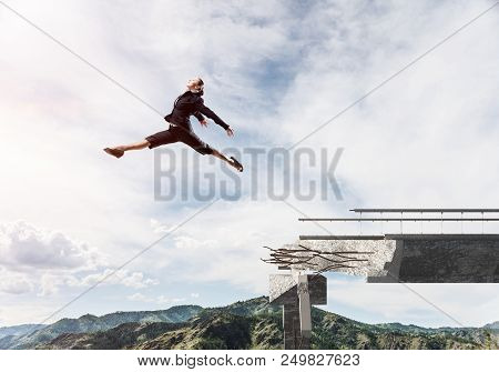 poster of Business Woman Jumping Over Huge Gap In Concrete Bridge As Symbol Of Overcoming Challenges. Skyscape