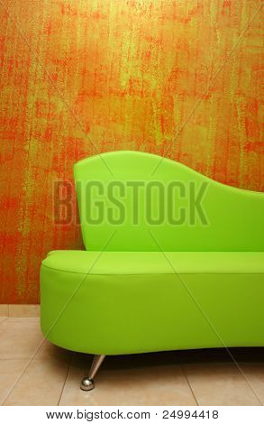 green sofa over a stylish red wall-paper background
