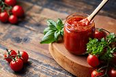 Homemade tomato sauce in a glass jar, tomatoes and herbs on its side. poster