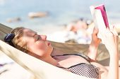 Woman Reading Book In Hammock On The Beach. Summertime Read. poster