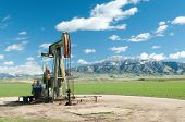 picture of derrick  - oil drill in green field with snow covered mountains in background