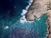 Aerial above rugged rocky coastline in stormy seas poster