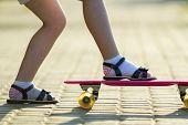 Child Slim Legs In White Socks And Black Sandals On Plastic Pink Skateboard On Bright Sunny Summer B poster
