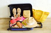 Open Suitcase Fully Packed With Folded Womens Clothing And Accessories On The Floor. Woman Packing  poster