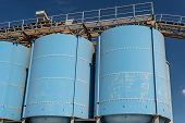 Big Blue Metallic Industrial Silos For The Production Of Cement At An Industrial Cement Plant On The poster