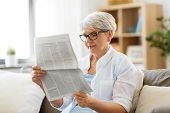 age and people concept - happy senior woman reading newspaper at home poster