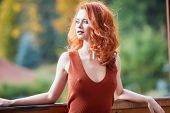 Beauty Romantic Girl Outdoors enjoying nature. Beautiful autumn red hair model with waving glow hair poster