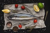Raw Fish And Cooking Ingredients On Parchment, Top View poster