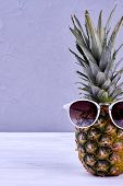 Hipster Pineapple With Sunglasses Against Grey Background. Fresh Pineapple Fruit In Sunglasses And C poster