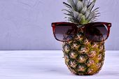 Ananas In Sunglasses And Copy Space. Fresh Realistic Pineapple Fruit Wearing Sunglasses On Wooden Ba poster