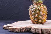 Composition From Pineapple And Natural Wood. Organic Ananas On Wooden Stump, Black Slate Background. poster