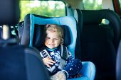 Adorable Baby Girl With Blue Eyes Sitting In Car Safety Seat. Toddler Child Going On Family Vacation poster