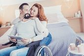 Loving Wife. Cheerful Loving Wife Gently Touching The Cheek Of Her Disabled Husband While Hugging Hi poster
