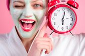 Facial Cosmetical Mask. Spa. Cosmetic Procedures. Woman With Cosmetic Mask On Face Holds Clock. Well poster