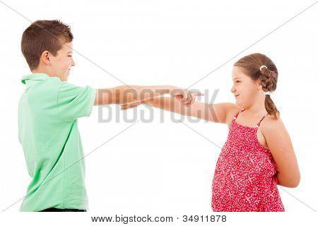 Dois filhos sorridentes apontando uns aos outros, isolado no fundo branco