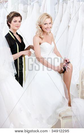 Future bride in wedding gown puts the garter