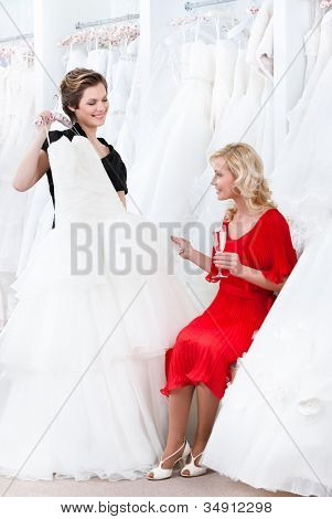 Shop assistant proposes another dress to the bride while she is drinking champagne