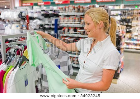 a young woman on the purchase of clothing in a single commision supermarket. assessment of quality.