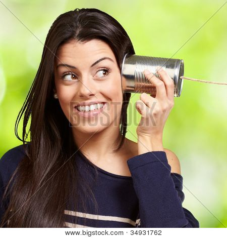 Young woman hearing using a metal tin can against a nature background