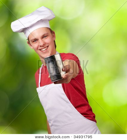 portrait of a young cook man holding a metal tin can against a nature background