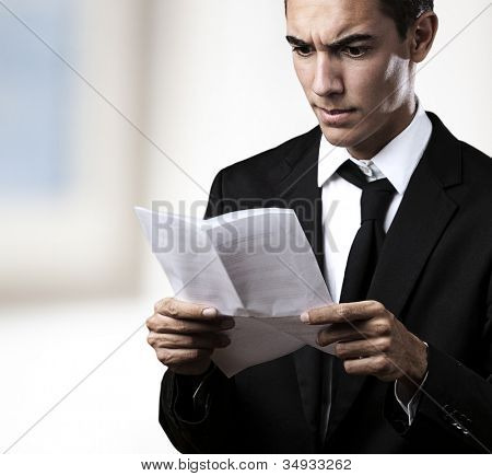 portrait of a young business man reading a contract in a house