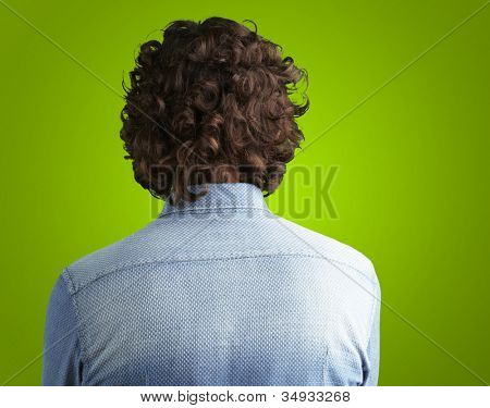 Back side view of a man against a green background