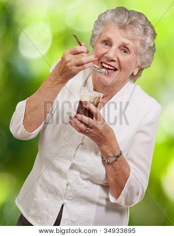 portrait of a senior woman eating a chocolate and cream cup against a nature background