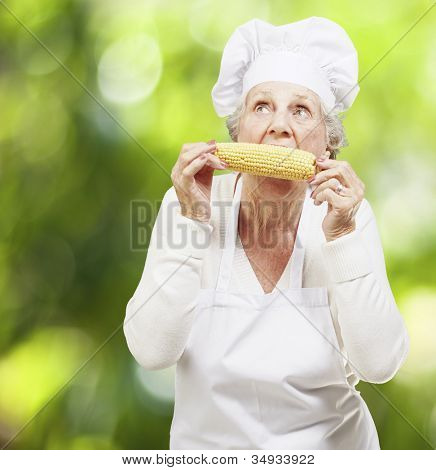 senior woman cook eating a corncob against a nature background