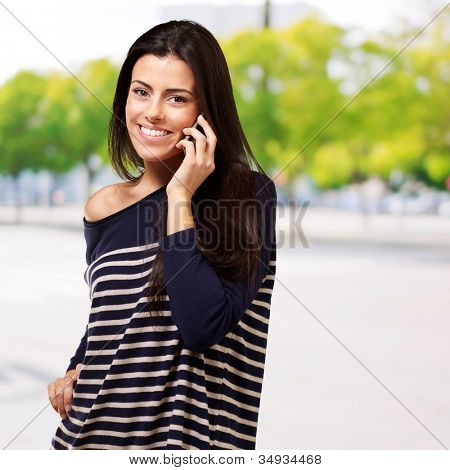 Young woman talking on a mobile against a plant background