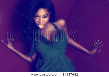 Beautiful feisty vivacious African dancer in a green dress with large curvy breasts enjoying herself