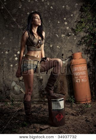 Dark moody portrait of a beautiful brunette woman in shorts and boots posing with an old propane cylinder and can against a grungy wall