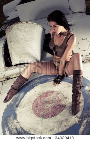 Sexy woman sitting on an aeroplane fuselage in skimpy shorts with her legs spread around an old airforce insignia