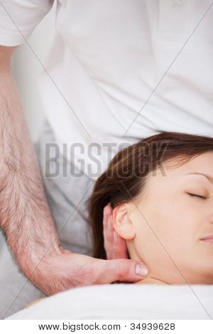 Close-up of woman being manipulating by a therapist in a room