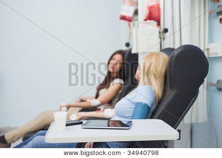 Two patients speaking in hospital ward