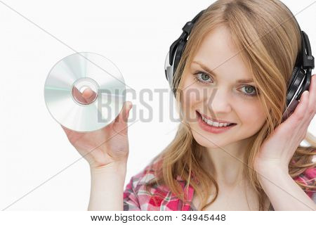 Woman holding a cd while looking at camera against a white background