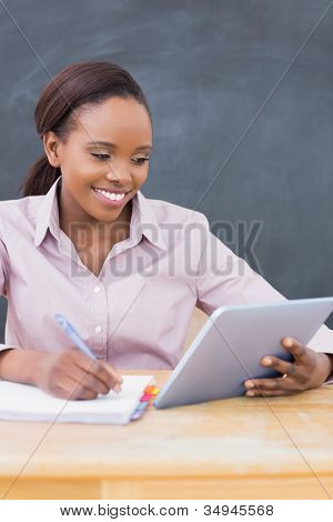 Teacher looking at a tablet computer in a classroom