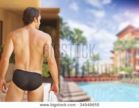 Beautiful sexy man with nice body from behind at glamorous resort swimming pool
