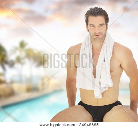 Portrait of a healthy good-looking guy in bathing suit with towel around his neck in beautiful spa resort setting