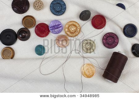 Set Of Colorful Sewing Buttons And Thread Reels On White Linen Fabric