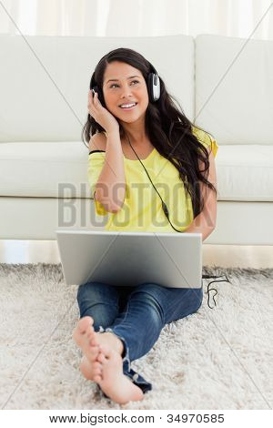 Pretty Latin listening to music on a laptop while sitting on the floor