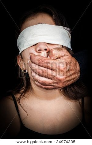 Small girl blinded with a handkerchief with an adult man hand covering her mouth on a black background