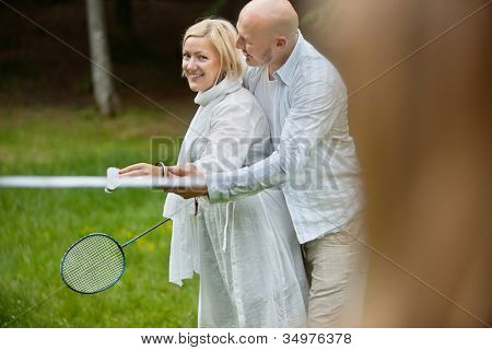 Portrait of mature couple in casual wear playing badminton together on a weekend outing