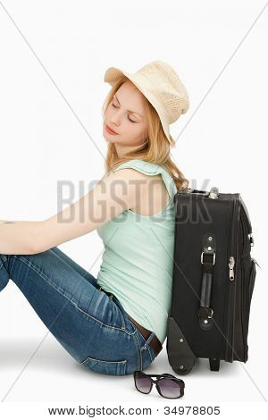 Blonde-haired woman sitting against a suitcase against white background