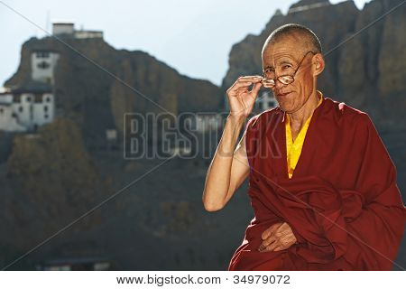 Indian tibetan old monk in red color clothing with glasses in front of monastery