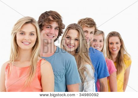 A smiling group standing behind each other at an angle while looking into the camera