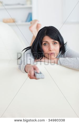 Woman pressing on a television remote while laying on a sofa in a living room